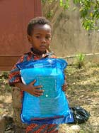 Child holding a mosquito net in Togo. There are still insufficient